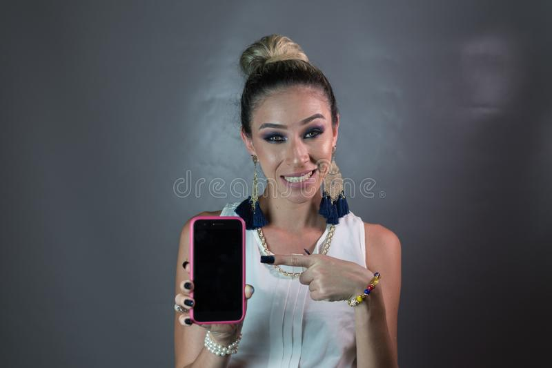A beautiful woman shows her cell phone with her finger. And smiles, has jewelry, long nails, green eyes stock image