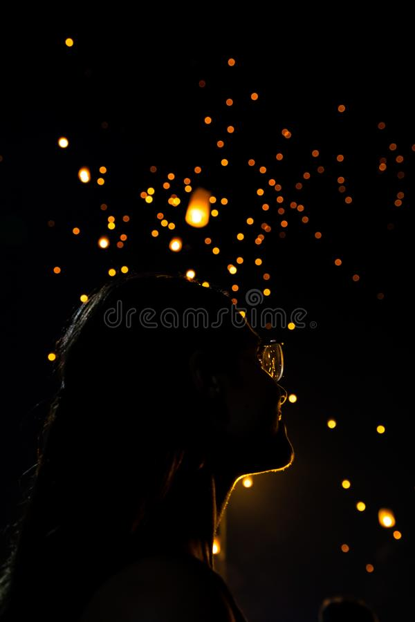 Beautiful woman silhouett portrait looking at Loy Krathong paper lanterns as bokeh on background in Thailand royalty free stock photos