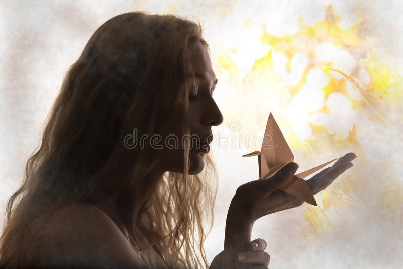 Beautiful woman silhouette and an origami crane on her palm royalty free stock photography