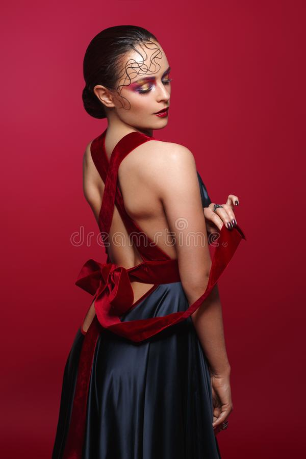 Beautiful woman in silk dress with red bow stock photo