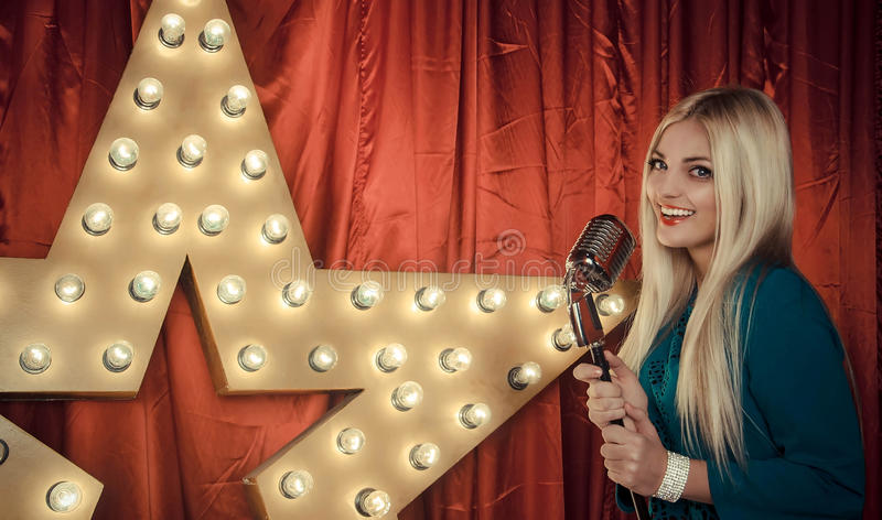 Beautiful woman singing on stage with microphone stock image