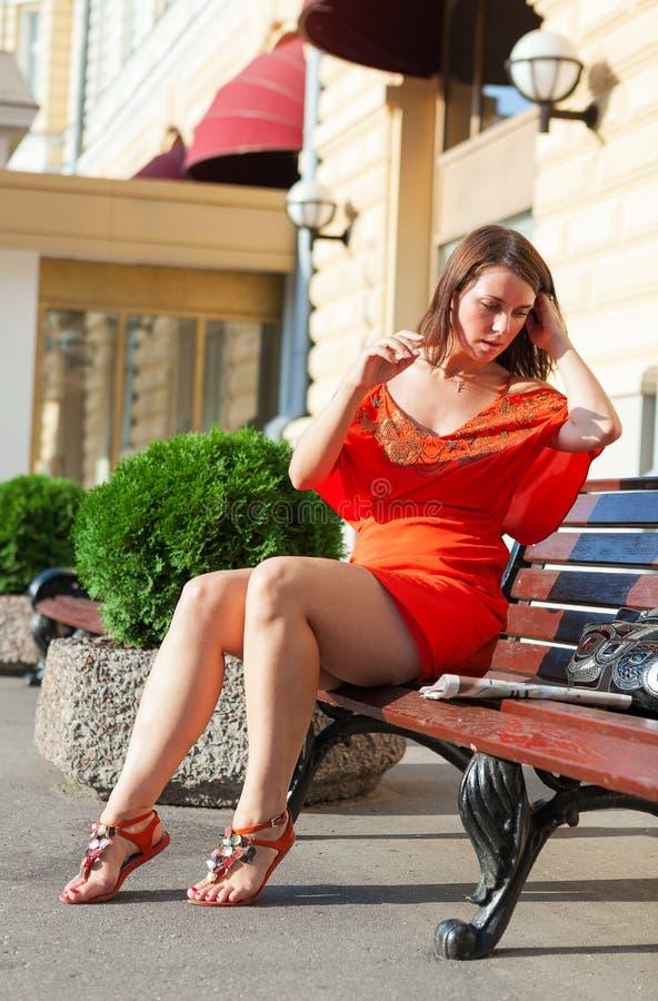 Beautiful woman sits on bench stock image