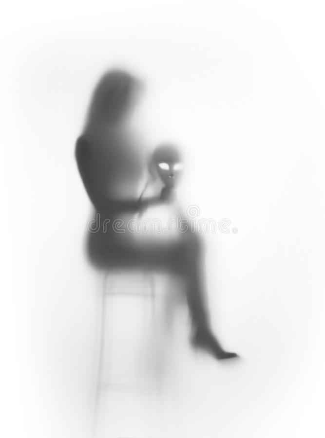Beautiful woman sits on chair with mask behind a glass surface stock photo