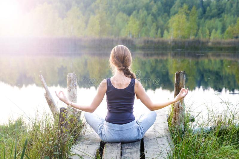 A beautiful woman sits in a pose of half lotus stock photo