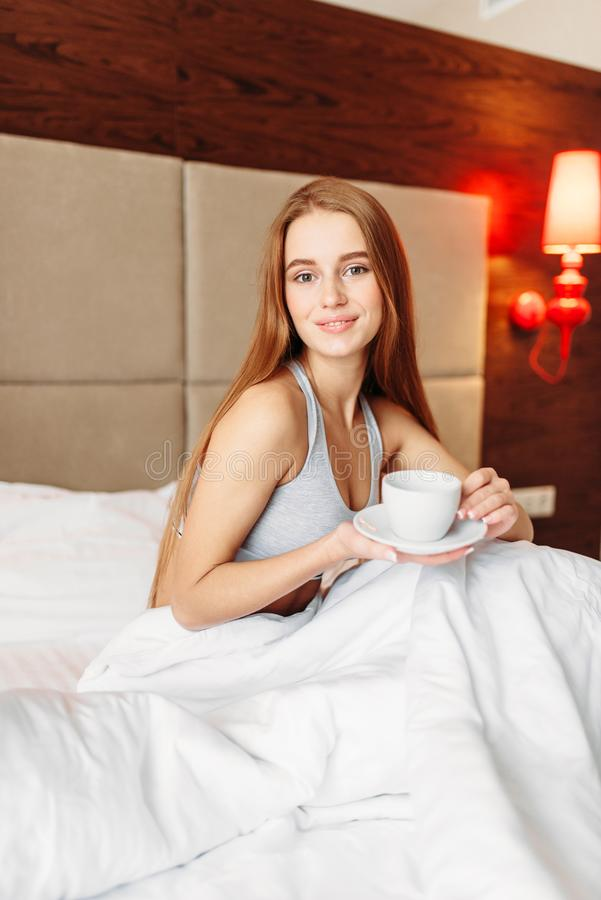 Beautiful woman sitting in bed with cup of coffee royalty free stock photos