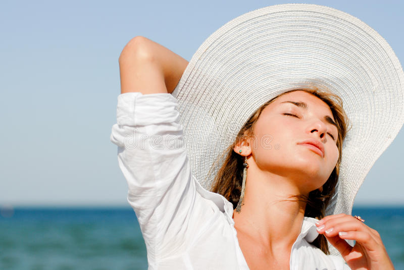 Beautiful woman sitting by blue sea & wearing hat. Young beautiful woman sitting outdoors in summer by blue sea and wearing white hat stock photo