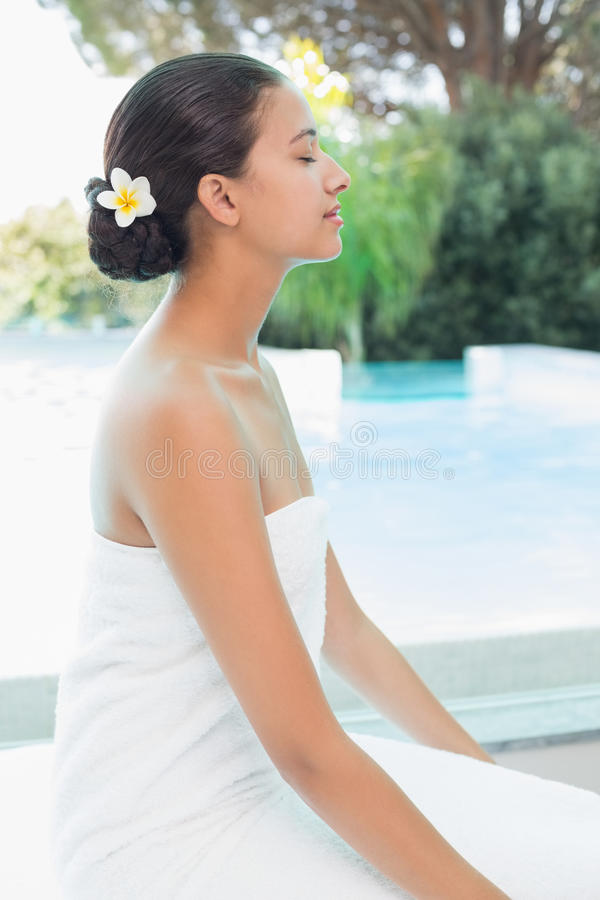 Beautiful woman sitting with eyes closed at spa center. Side view of a beautiful young woman sitting with eyes closed at spa center stock photo