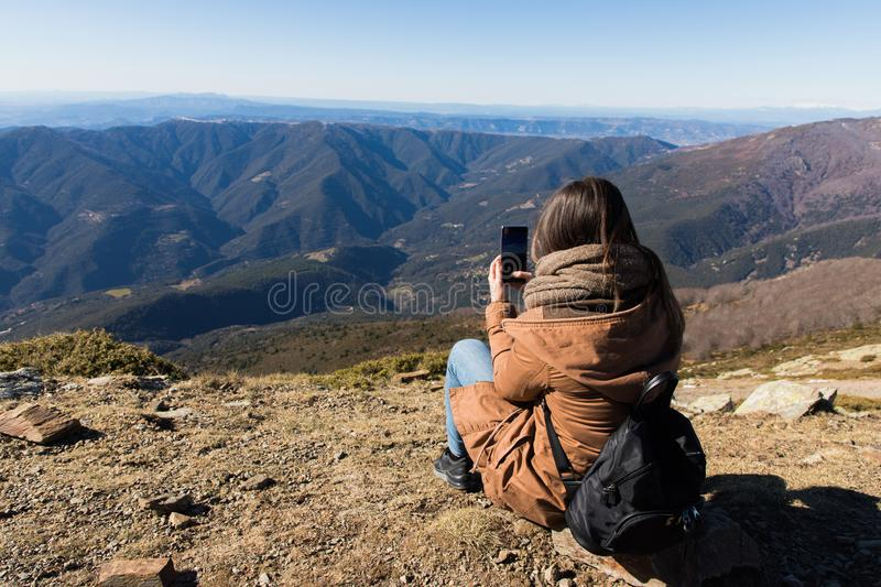 Beautiful woman sitting after hiking and taking photo with phone during winter or autumn in Catalonia royalty free stock images