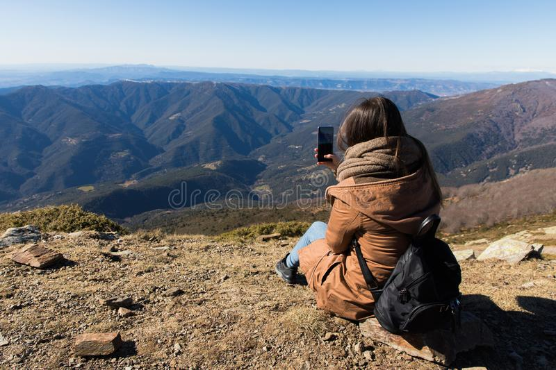 Beautiful woman sitting after hiking and taking photo with phone during winter or autumn in Catalonia stock photography