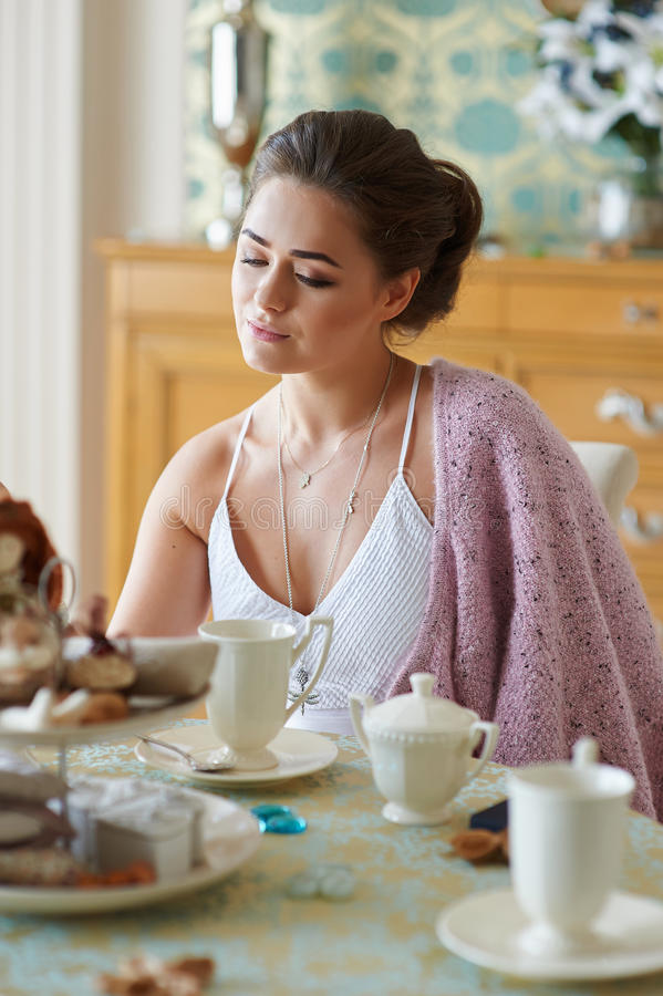 Beautiful woman sitting in the kitchen in the morning and drinking tea royalty free stock photography