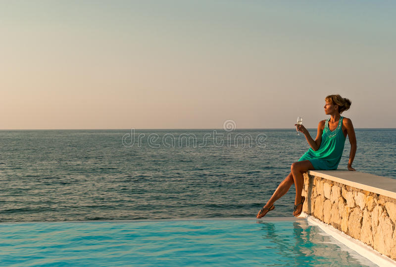 Download Beautiful Woman Sitting Near Infinity Pool Stock Image - Image: 22982729