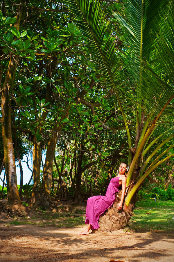 Beautiful Woman Sitting On The Palm Royalty Free Stock Photos