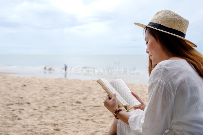 A beautiful woman sitting and reading book on the beach stock images