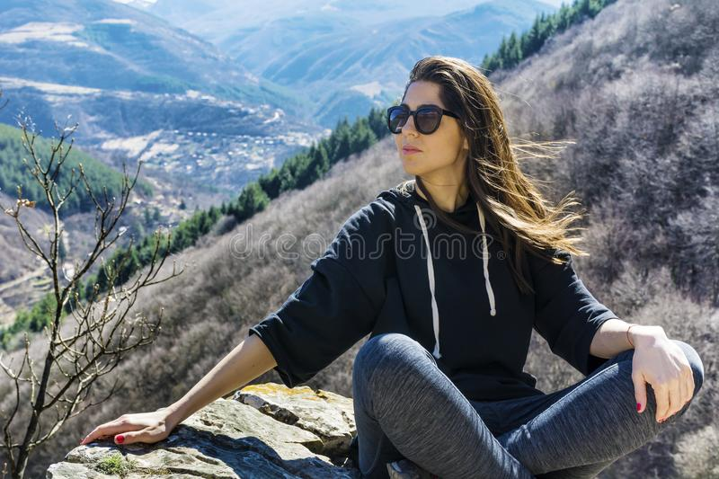 Beautiful Woman Sitting on a Stone in a High Mountain. Happy woman relaxing in a high mountain stock photos