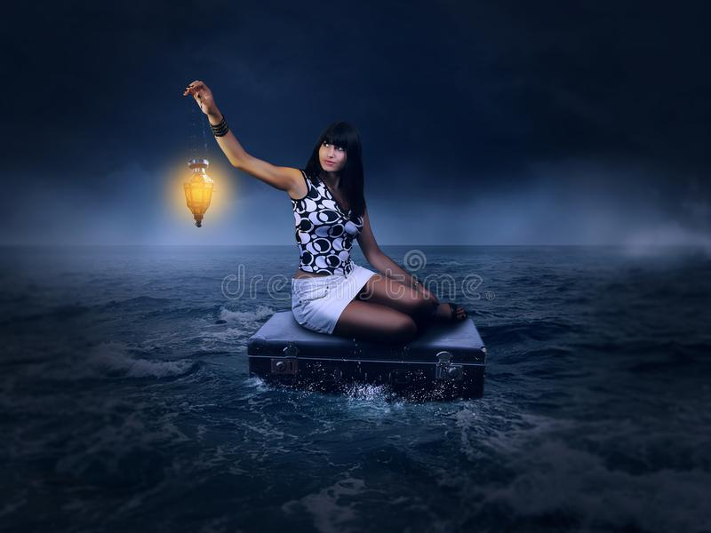 Fantasy concept . beautiful woman sitting on a suitcase alone in the sea stock photos
