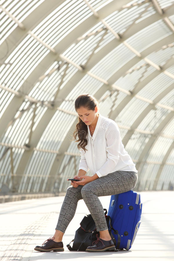 Beautiful woman sitting on suitcase using mobile phone stock images