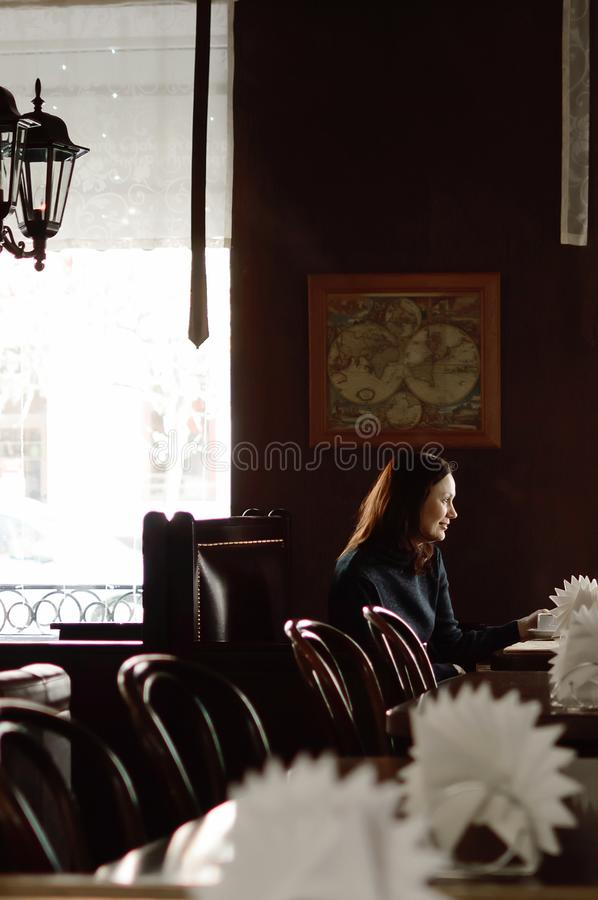 A beautiful woman is sitting at a table in a cafe. The modern interior of the restaurant. A beautiful woman is sitting at a table in a cafe. The modern interior royalty free stock image