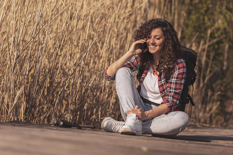 Woman having a phone conversation outdoors. Beautiful woman sitting on the wooden lake docks, enjoying an autumn day in nature, relaxing after hiking and having royalty free stock photography