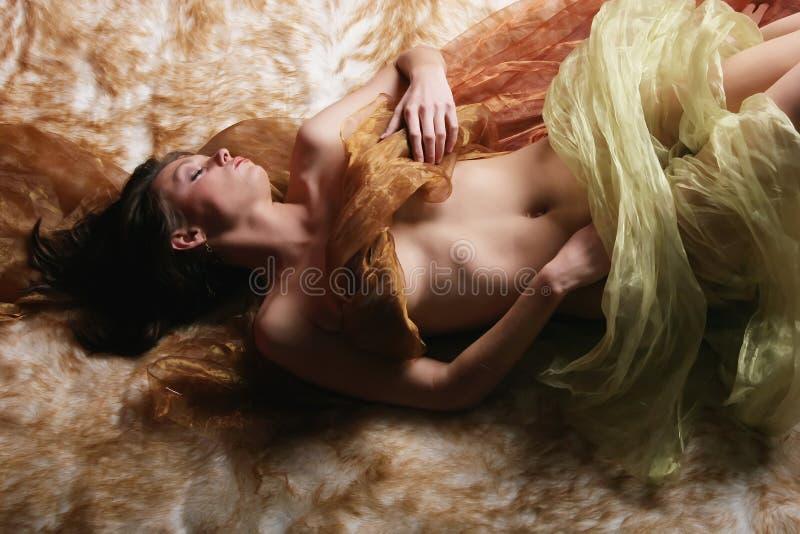 Beautiful woman sleeping. Woman wrapped in silk sleeping royalty free stock image