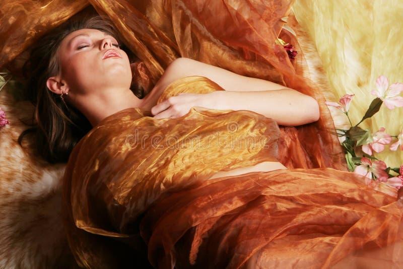 Beautiful woman sleeping. Woman wrapped in silk sleeping stock photo
