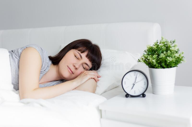 Beautiful woman sleeping in bed at home, alarm clock on bedside table stock image