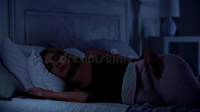 Beautiful woman sleeping with smartphone in hands, gadget addiction, application. Stock photo royalty free stock photos