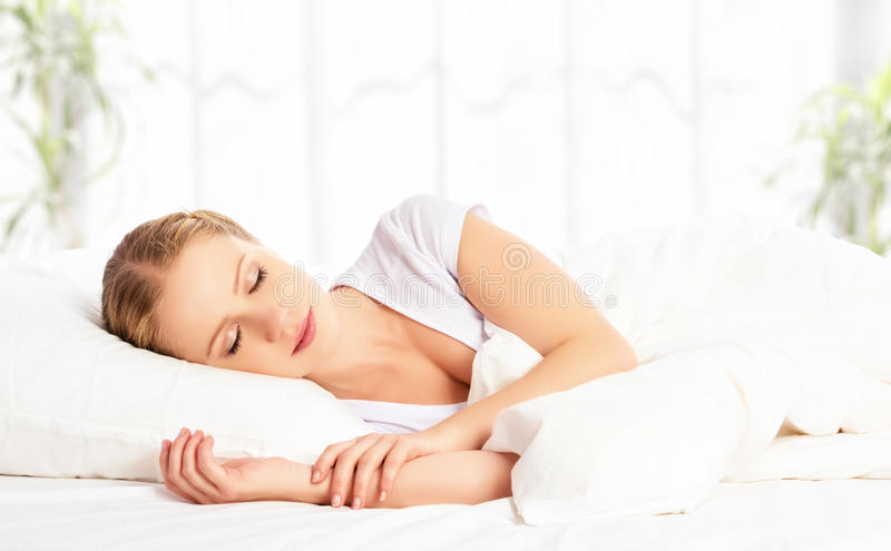 Beautiful woman sleeping and smiles in his sleep in bed stock photos