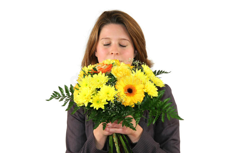 Beautiful woman smelling at a bunch of flowers. A beautiful young business woman smelling at a bunch of flowers with closed eyes, isolated on white background royalty free stock photography