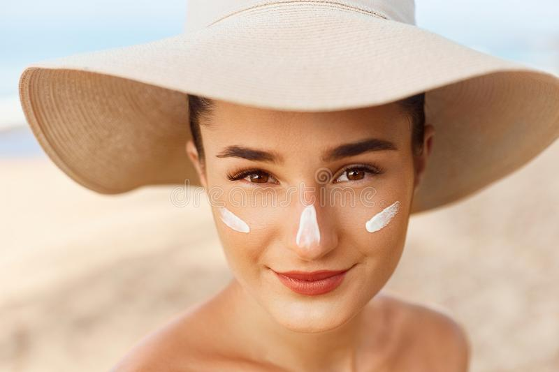 Beautiful Woman smile applying sun cream on face. Skin and  Body  care. Sun protection. Girl in bikini holding sunscreen bottle on the beach. Female in hat royalty free stock photo