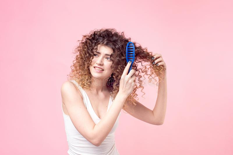 Beautiful woman with a smile on her face with curly hair in a white T-shirt combing blue curls with a blue comb isolate royalty free stock photography