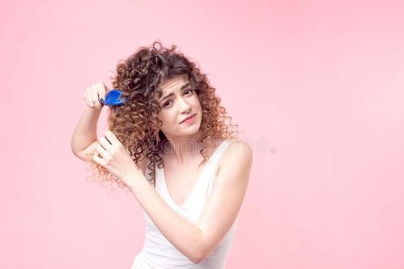 Beautiful woman with a smile on her face with curly hair in a white T-shirt combing blue curls with a blue comb isolate stock photos