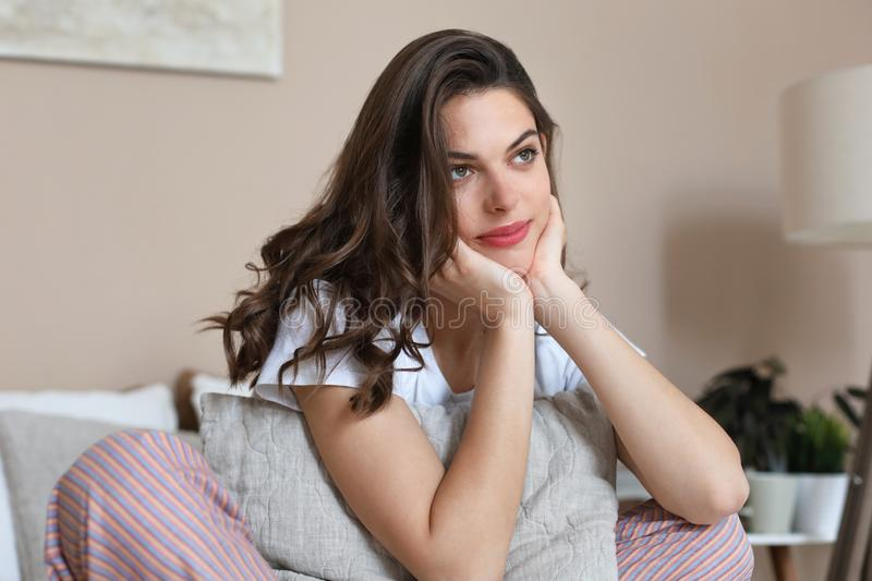 Beautiful woman is smiling daydreaming and relaxing in bed royalty free stock photos