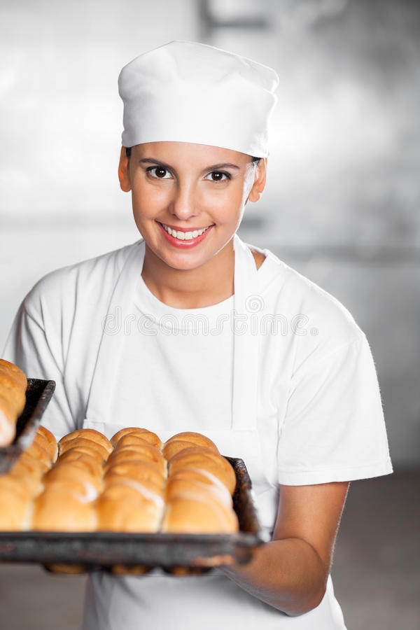 Beautiful Woman Smiling While Holding Bread Tray In Bakery stock photography