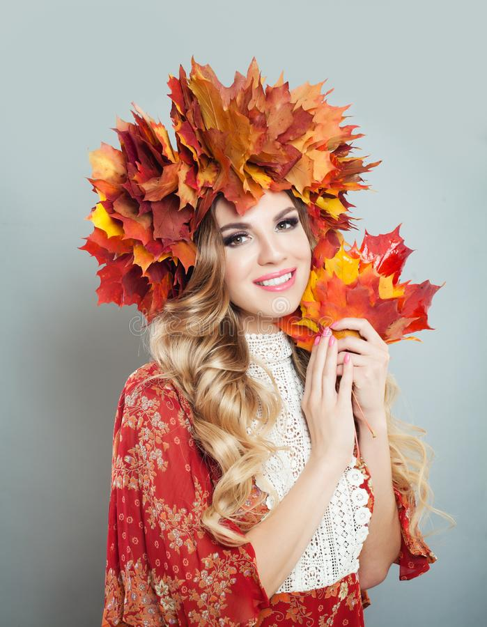 Beautiful woman smiling and holding fall leaves in hands. Pretty model with makeup, curly hair, autumn leaves crown.  royalty free stock photos