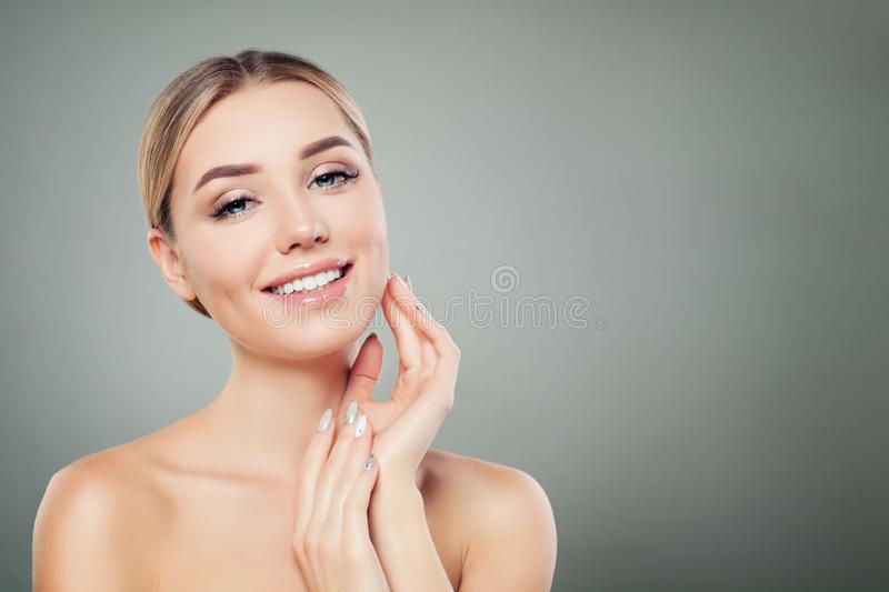 Beautiful woman smiling and touching her hand her face. Cute girl with clear skin. Facial treatment, face lifting and cosmetology royalty free stock photo