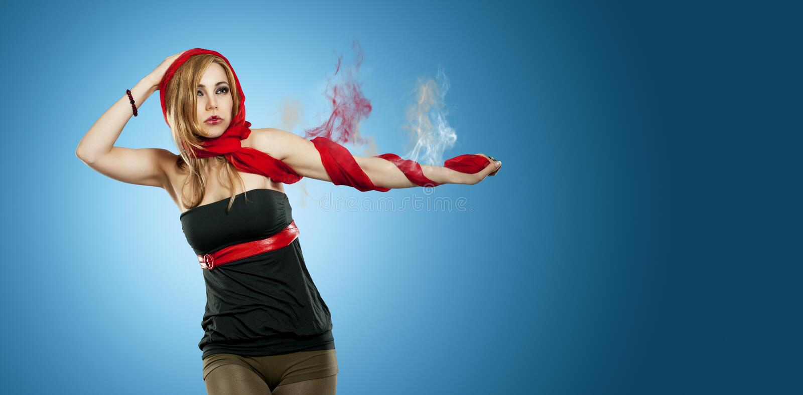 Beautiful woman with a smoking arm. Beautiful woman with red scarf in front of a blue background and a smoking arm royalty free stock photos