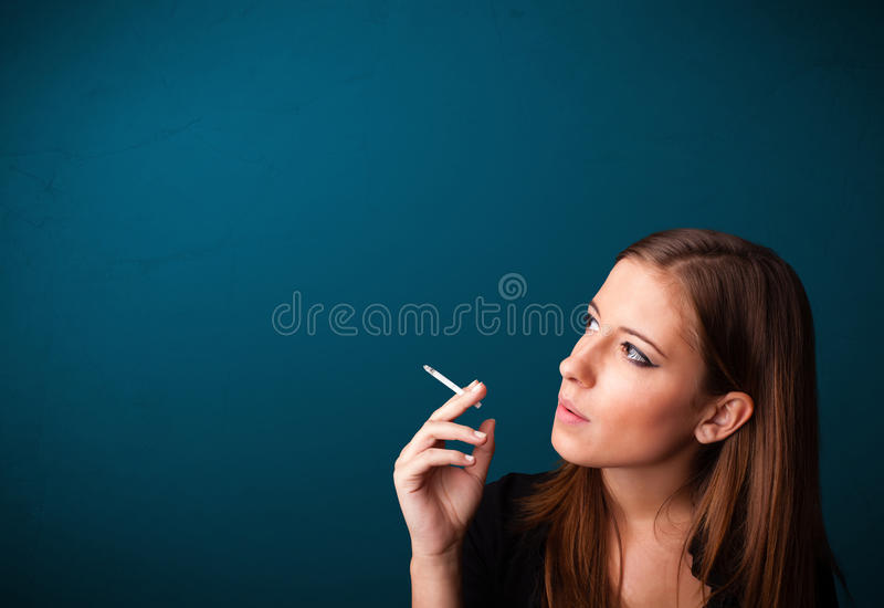Beautiful woman smoking cigarette vith copy space. Beautiful young woman smoking cigarette with copy space royalty free stock image