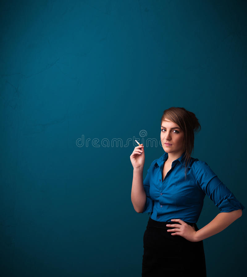 Beautiful woman smoking cigarette vith copy space. Beautiful young woman smoking cigarette with copy space royalty free stock photography