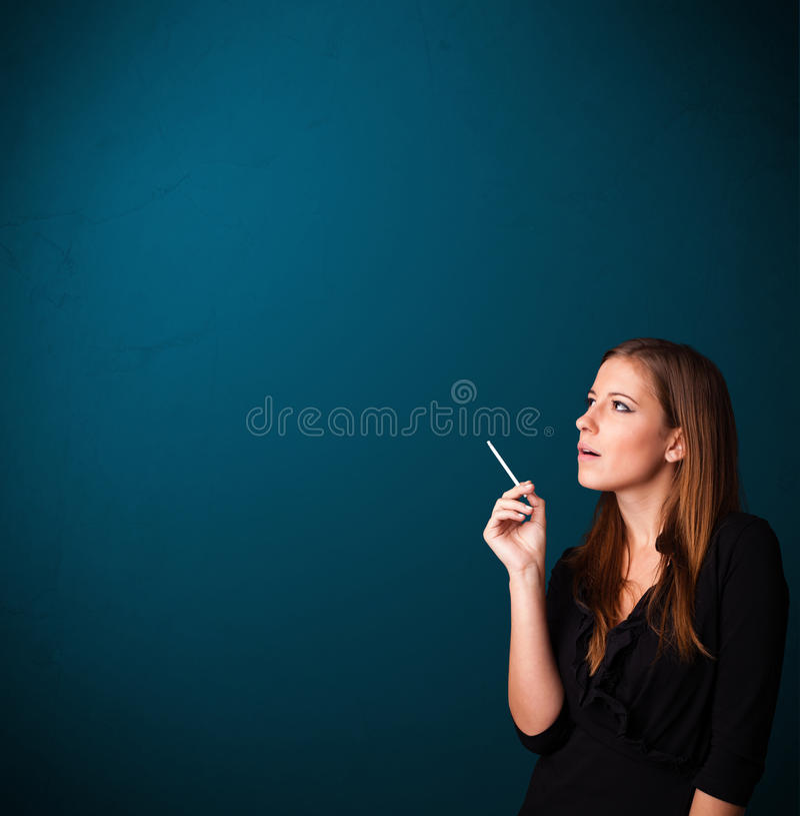 Beautiful woman smoking cigarette vith copy space. Beautiful young woman smoking cigarette with copy space royalty free stock photo