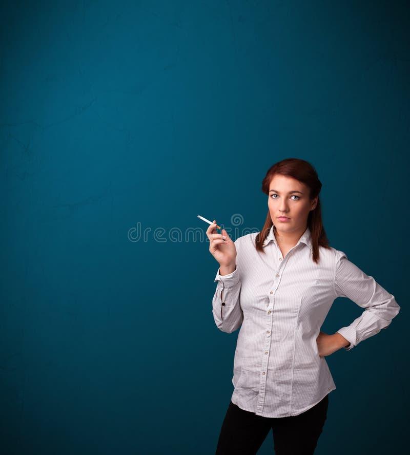 Beautiful woman smoking cigarette vith copy space. Beautiful young woman smoking cigarette with copy space royalty free stock photos