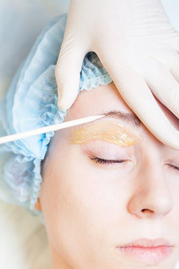 Beautiful woman in spa salon receiving epilation or correction eyebrow. Closeup beautiful woman in spa salon receiving epilation or correction eyebrow using stock photography
