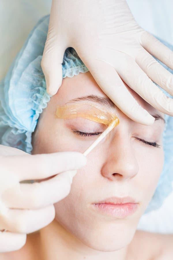 Beautiful woman in spa salon receiving epilation or correction eyebrow. Closeup beautiful woman in spa salon receiving epilation or correction eyebrow using royalty free stock image
