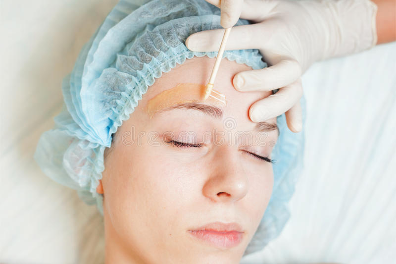 Beautiful woman in spa salon receiving epilation or correction eyebrow. Closeup beautiful woman in spa salon receiving epilation or correction eyebrow using royalty free stock images