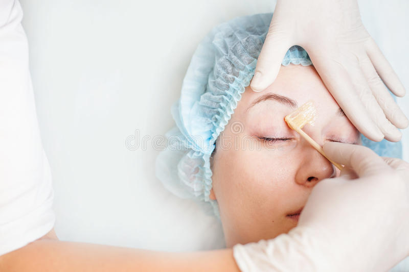Beautiful woman in spa salon receiving epilation or correction eyebrow. Using sugar - sugaring. You can see her smooth eyebrow after hair removal royalty free stock images