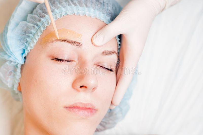 Beautiful woman in spa salon receiving epilation or correction eyebrow. Using sugar - sugaring. You can see her smooth eyebrow after hair removal stock photo