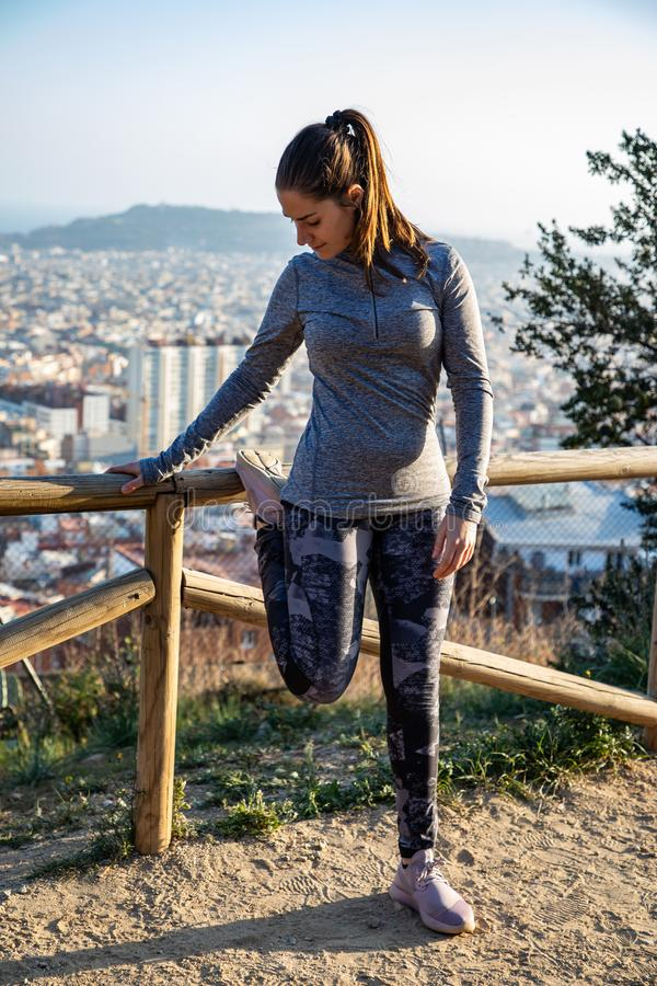 Beautiful woman in sport outfit stretching in park with the city of Barcelona blurred in background royalty free stock image