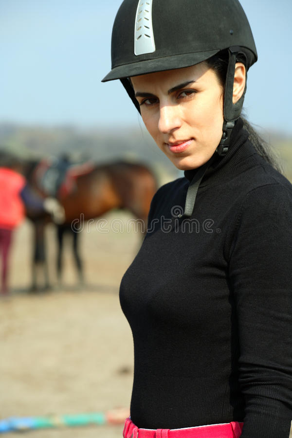 Beautiful woman on sportswear and a helmet. (equestrian sport), background royalty free stock image