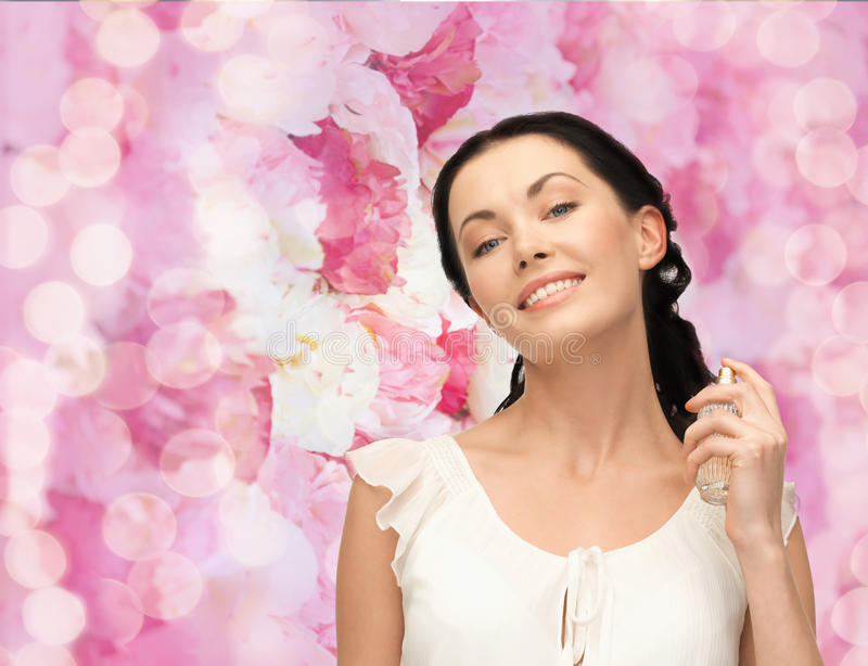 Beautiful woman spraying pefrume on her neck stock images