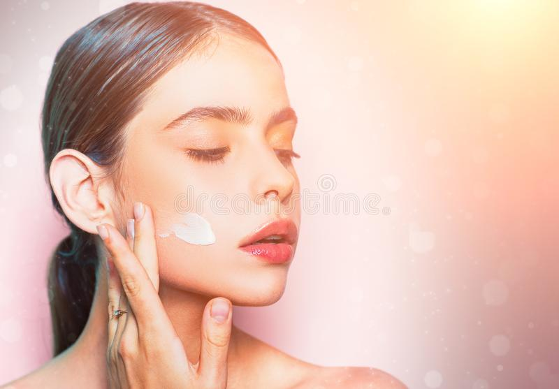 Beautiful woman spreading cream on her face. Skin cream concept. Facial care for female. Keep skin hydrated regularly stock photo
