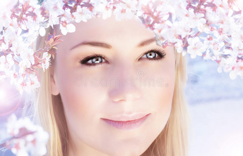 Beautiful woman in spring. Picture of beautiful woman outdoors in spring time, closeup portrait of cute blonde female wearing pink floral wreath, cherry blossom stock photography